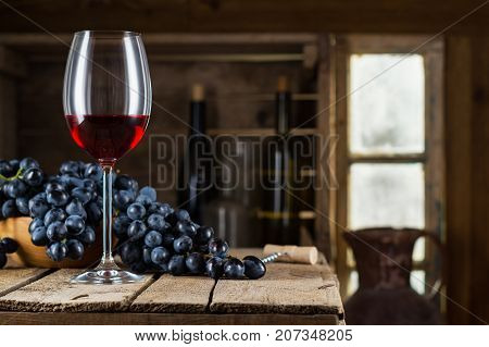 Still life of red wine with wooden keg. Wine bottle glass of red wine and grape on a old wooden barrel. Wine tasting and production concept.