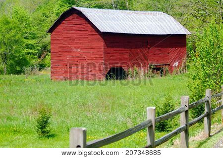 A red barn in a post fenced pasture.