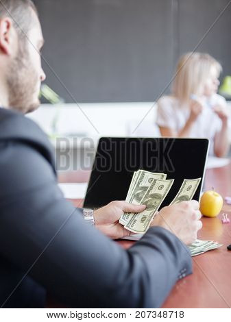 The young boss considers the salary of money for employees. Group of young modern people in smart casual wear having a brainstorm meeting while sitting behind the glass wall in the creative office. Close-up of hands with money. Business concept.