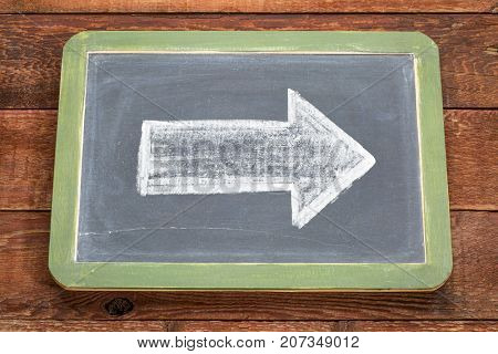 arrow - white chalk drawing on a vintage slate blackboard with red barn wood background