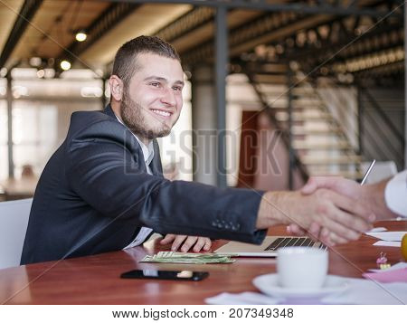 The young boss shaking hands with his partner. Group of young modern people in smart casual wear having a brainstorm meeting while sitting behind the glass wall in the creative office. Close-up of hands with money. Business concept.