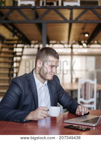 The young boss working and drinking coffe. Group of young modern people in smart casual wear having a brainstorm meeting while sitting behind the glass wall in the creative office. Close-up of hands with money. Business concept.