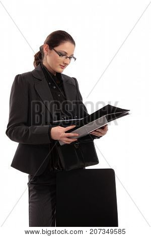 Attractive young businesswoman in suit holding folders, reading them, looking down, smiling. Isolated on white.