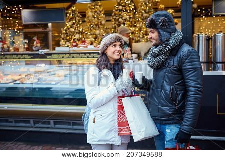 Young couple having hot drink at wintertime on the street.