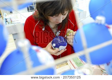Lubyanka,Kiev region,Ukraine, December 05, 2009:The girl paints on a glass ball, for New Year's holiday. Factory of Christmas-tree toys