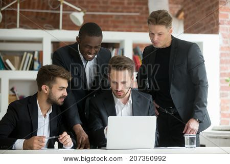 Multiethnic team of corporate employees looking at laptop screen. Businessman pointing at computer screen, african american colleague smiling. Group of coworkers discussing investment opportunities.