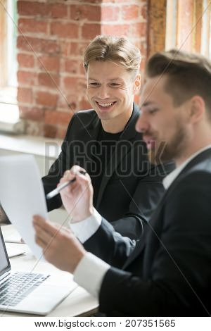 Two handsome smiling business coworkers looking at paper documents at work in office. Businessmen analyzing positive financial report results. CEO and project manager happy with investment outcome.