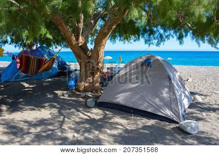 Tents under the tree shadow at the amazing tropical beach of Panagia Tripiti, in Crete, with sandy beach, turquoise water and some lucky campers, Greece.