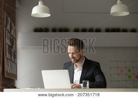 Young cheerful business man sitting in modern office, looking at laptop with happy smile, pleased with successful deal, financial report, project results and stock investment profit. Success concept.