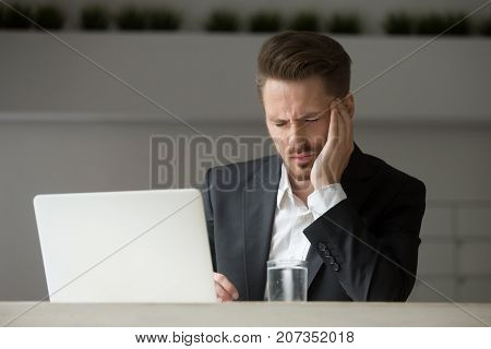 Stressed businessman not feeling well, has bad headache at work. Project manager got dizzy having too much work before deadline Being sick at work, lack of rest, overworked, stress induced migraine.