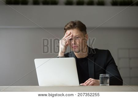 Exhausted businessman looking at laptop with hand on his forehead. Project manager tired of heavy workload, not happy seeing negative financial investment results. Stressful day, difficult work task.