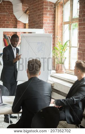 Young confident african american business coach explaining drawn chart to team of coworkers. Employees learning about improvements in company workflow during important meeting, . Corporate briefing.