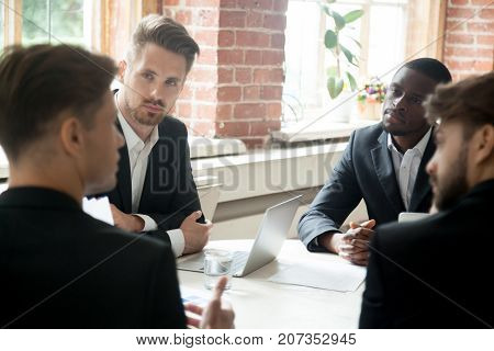 CEO discussing corporate matters with group of employees. Boss consulting group of coworkers during briefing meeting. Project manager talking about company goals to team of multiethnic colleagues.