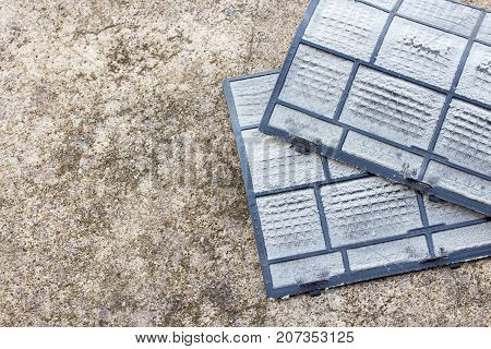Dirty dust filters of air conditioner ready for cleaning on the ground. Home and air conditioner service concept.