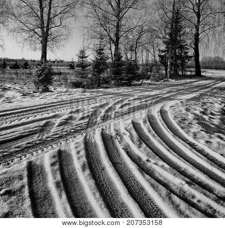 Winter road with traces of car tire tread. Snow-covered road after last snowfall. Country road. Roadway small size. Wheel tracks on the winter road covered with snow. Photo closeup in winter. Black and White.