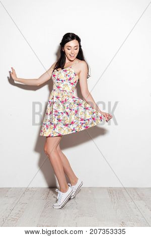 Full length image of pleased brunette woman in dress dancing in studio and looking down over white background