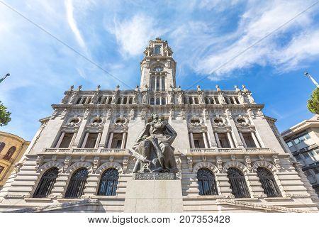Bottom view of majestic facade of Porto City Hall or Camara Municipal do Porto in Avenida dos Aliados, Liberty square, Oporto in Portugal. Sunny day in the blue sky.