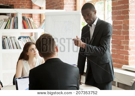 African American employee behaving rudely during briefing meeting. Disgruntled corporate worker expressing frustration to his coworkers. Angry businessman unhappy with unproductive meeting result.