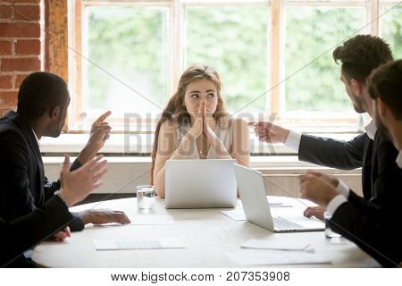 Perplexed young woman looking at coworkers pointing fingers at her. Disgruntled multiethnic team scolding female colleague who made bad work-related mistake. Stressed upset business lady in trouble.