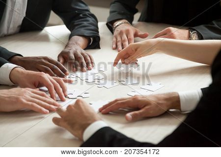 Close up of multiethnic team solving blank puzzle on table. Female hand offering puzzle piece, problem solution concept. Multi-racial executive employees brainstorming about work related problem.