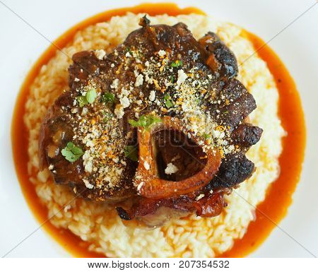 Osso buco is a Milanese speciality of cross-cut veal shanks braised with vegetables white wine and broth. It is garnished with gremolata and traditionally served with risotto alla milanese.
