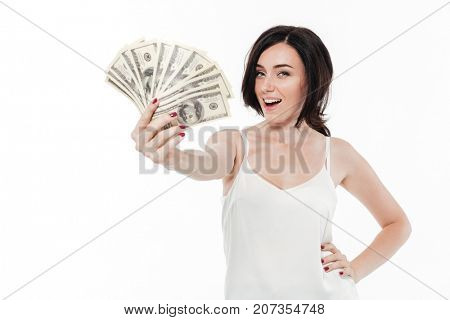 Portrait of an excited happy woman showing bunch of money banknotes isolated over white background