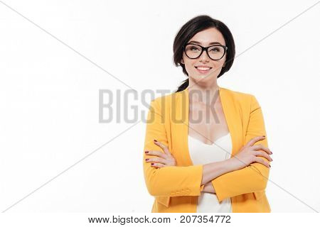 Portrait of a smiling attractive woman in eyeglasses and a jacket standing with arms folded and looking at camera isolated over white background