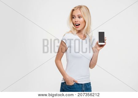 Photo of beautiful blonde woman with open mouth and hand in the pocket, showing blank smartphone screen, isolated on white background