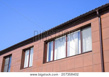 Plastic Windows On The House And A Spillway System On The Roof. House With Plastic Windows And A Bro