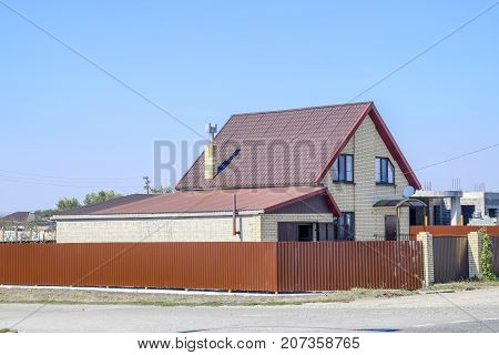 House With Plastic Windows And Roof Of Corrugated Sheet. Roofing Of Metal Profile Wavy Shape On The
