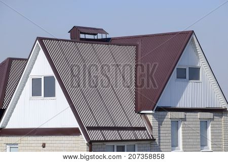 The House Is With An Attic And A Combined Roof. House With Plastic Windows And A Brown Roof Of Corru