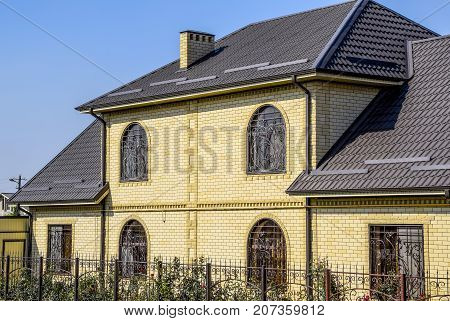 House Of Yellow Brick And Brown Corrugated Roof Made Of Metal. Lattices On The Windows.