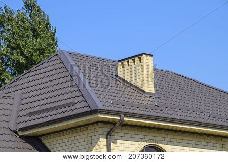 Brown Corrugated Metal Profile Roof. Chimney And Ventilation Of Yellow Brick.