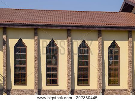 Building With Yellow Walls And A Red-brown Roof. Modern Materials Of Finish And Roofing.