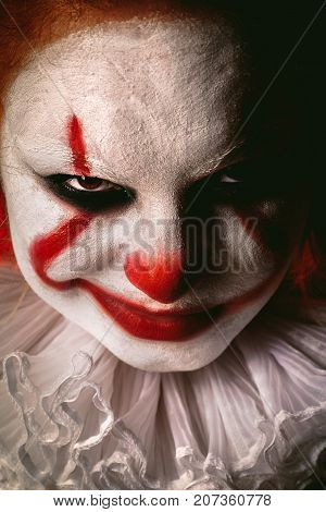 angry evil clown face looking at camera close up