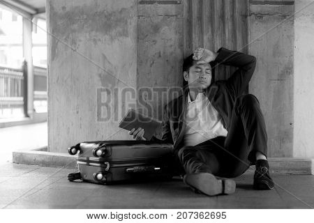 Stressed Asian Businessman Bankrupt With Sitting At Outdoor.