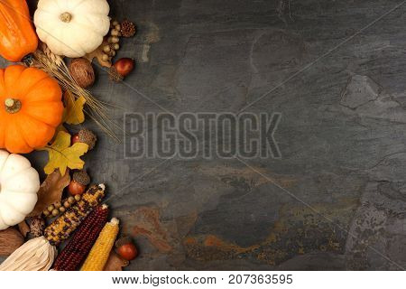 Autumn Harvest Side Border With Pumpkins, Leaves And Nuts Over A Slate Stone Background