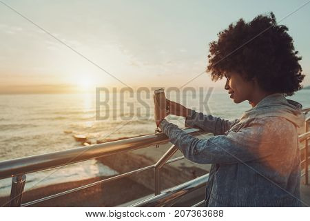 Curly young smiling biracial girl in jean jacket is leaning on chrome railing while standing on the sea-front and taking picture of stunning sunset and horizon over water using her smartphone