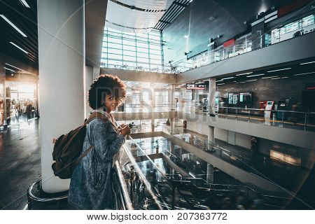 Cheerful young black tourist woman is leaning on chrome railing while standing inside of glossy interior of huge modern multi-story hall of airport terminal or railway station