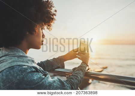 Close-up side view of beautiful young African American lady with curly afro hair leaning her hands on chrome railing and shooting dramatic sunset over the sea using back camera of her smartphone
