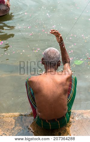 VARANASI INDIA - MARCH 14 2016: Vertical picture of indian people bathing with holy water of Ganges River during day time in Varanasi India.