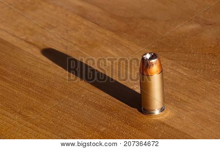 A single ,40 caliber hollow point bullet on a wooden table casting its shadow behind it