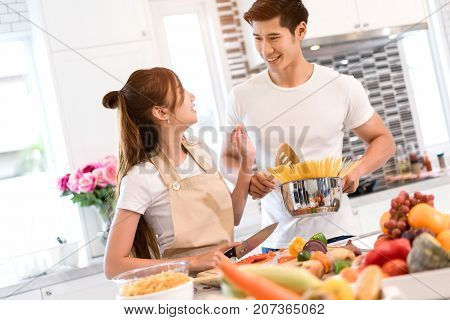 Young asian woman cutting slice vegetables making salad healthy food with fruits and man cooking menu for dinner in kitchen at home couple together romantic