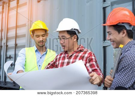 Three Engineer men with safety helmet teamwork building consult project looking paper plan in side construction with level
