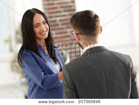 Smiling businesswoman communicating with male colleague in the o