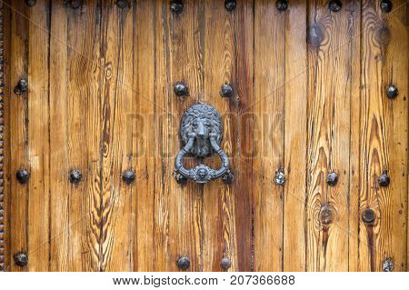 Lion Head Door Knocker on aged wooden door with knobs