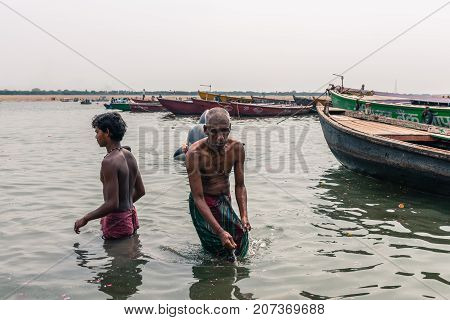 VARANASI INDIA - MARCH 14 2016: Wide angle picture of indian people bathing with holy water of Ganges River during day time in Varanasi India.