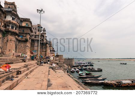 VARANASI INDIA - MARCH 14 2016: Horizontal picture of the stairs of Munshi Ghat and many boats at Ganges River in the city of Varanasi in India