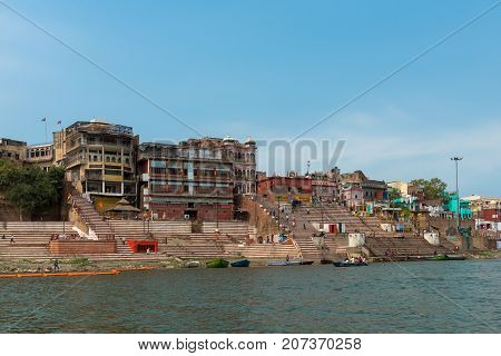 VARANASI INDIA - MARCH 14 2016: Wide angle picture of riverbank with many stairs of the Ghat in front of Ganges River in the city of Varanasi in India