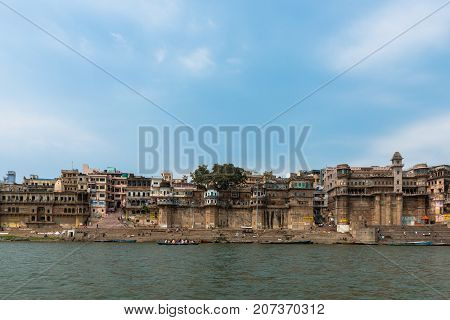 VARANASI INDIA - MARCH 14 2016: Wide angle picture from the boat of Chousat and Digpatiya Ghat in front of Ganges River during sunny day in the city of Varanasi in India